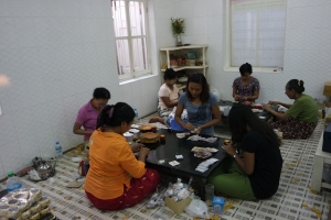 Women placing the gold leaves into small packages for the sale.